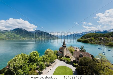 Spiez castle with sailboat on lake Thun in Bern Switzerland.