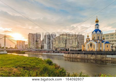 BELGOROD RUSSIA - JULY 04 2016: Belgorod cityscape on the sunset. Belgorod State University Embankment overlooking the temple of Archangel Gabriel and student residence.