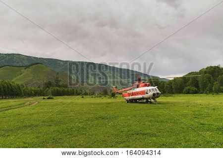 helicopter in the mountains on the field in the summer in a thunderstorm