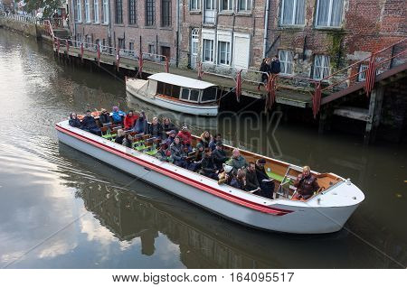 Ghent, Belgium - 19, 2016:  Tourists view the city on a sightseeing boat in Ghent, Belgium