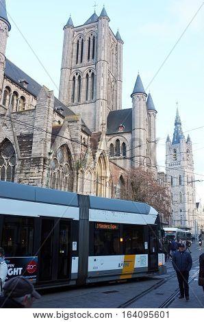 London, UK - November 19, 2016: Public tram runs in front of Saint Nicholas' Church in the centre of Ghent, Belgium