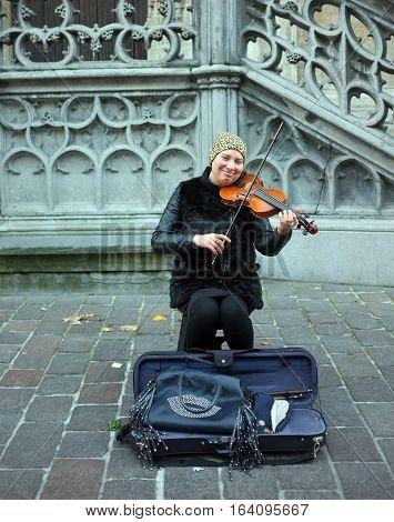 London, UK - November 19, 2016: Street musician plays violin on the street in Ghent, Belgium