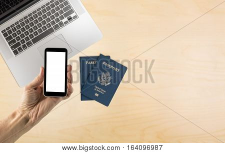 Male hand holding a smartphone with a blank screen over organized desk with laptop and USA passports