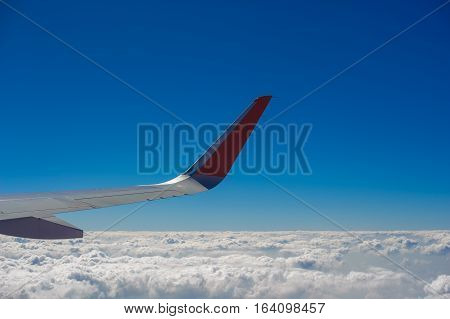 Aerial view of airplane flying above shade clouds and sky from an airplane fly. View from the plane window of emotional moment during international travel around the world.