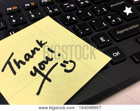 Thank you note on office computer keyboard handwritten with smile to thank employee, co-worker or colleague and express appreciation with hashtag key #thankyou an s words appreciation