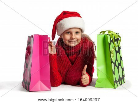 Girl In Santa Claus Hat With Shopping Bags