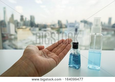 alcohol bottle and anti-bacterial hand gel on woman left hand