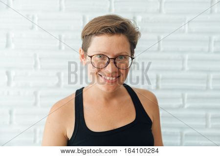 natural beauty. portrait of a young beautiful attractive girl. Short hair, no makeup, wearing glasses to view hipster style.