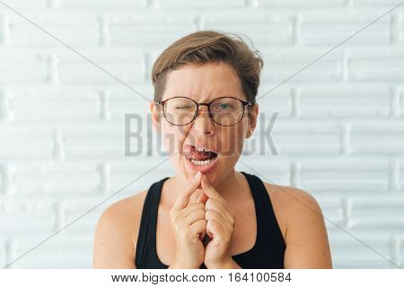girl with glasses and short hair ape at the camera, White background brick natural light from the window.