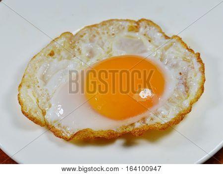 fried egg with creamy yolk on white dish