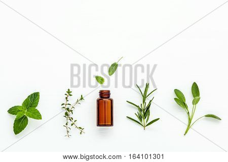 Bottle Of Essential Oil With  Fresh Herbal Sage, Rosemary, Lemon Thyme And Peppermint Setup With Fla
