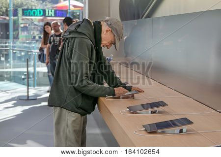 New York October 5 2016: An elderly man is looking at an iPad tablet in the Apple store on Manhattan's Upper West Side.