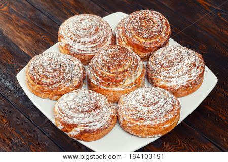 Sweet roll buns with shugar powder on wooden table