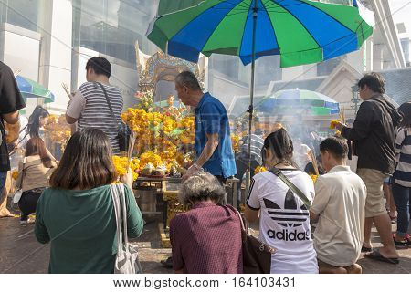 BANGKOKTHAILAND - DEC 31 : scene of people pray at Erawan shrine in ratchaprasong area on december 31 2016 Thailand. there are many tourist worship at Erawan shrine in new year festival