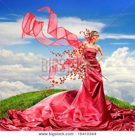 긴 빨간 드레스를 입고 아름 다운 여 자가 보유 하 고 이국적인 꽃 손