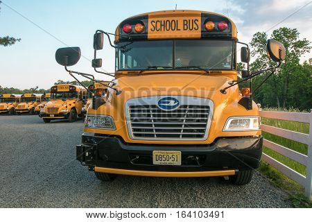 Somerset County, New Jersey, May 29, 2016: School buses are parked in a school bus parking lot by a field on a Sunday.