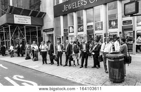 New York August 2 2016: People are lined up at a bus stop at the end of a work day near the Diamond District on 47th street.