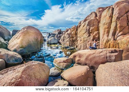 Woman sat in meditation pose on the stone in a rocky Norwegian coast