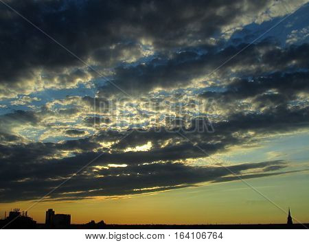 Beautiful strato-cumulus sunset with silhouettes of buildings and a church steeple