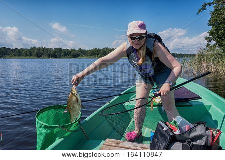 Fisher-woman caught fish and puts it in the tank