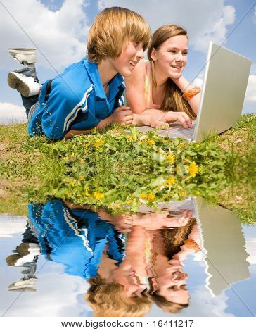 Two Smiling teenagers with laptop resting on meadow. Reflected in water