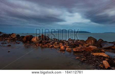 A cloudy evening sky over the south china sea with a rock formation and vinpearl island in the distance, Vietnam.