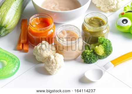 baby mashed with spoon in glass jar on white background close up