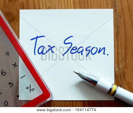 Tax Season written on paper note with pen and calculator - Business concept.