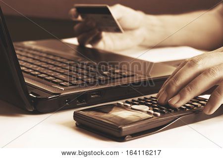 Young Man Calculating And Holding Credit Card With Laptop  About Cost For Shopping Online.