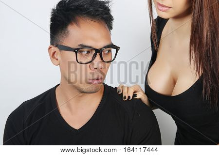 Young woman seducing a man with her breast over a white background
