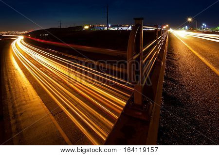 Busy car traffic trails on overpass and freeway at night