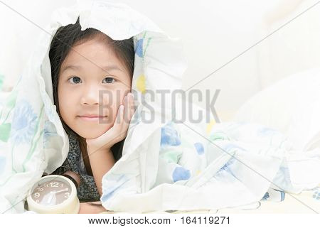 Adorable little cute girl awaked up in her bed with alarm clock