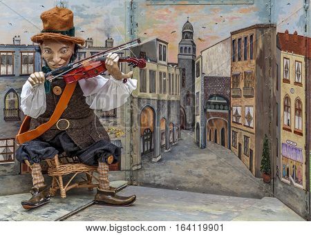 Portugal, Porto . Puppet show on one of the pedestrian streets . Poor violinist .