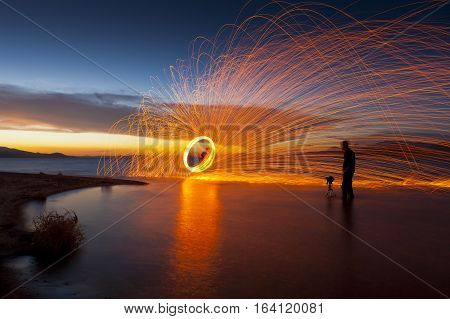 Photographer in lake shooting picture of spinning sparks at sunset. Pyramid Lake NV.