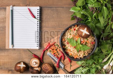 instant noodle with fresh vegetables on wood background fast food with notebook