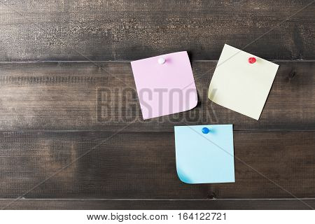 Color Paper Note With Pin On Old Wood Background