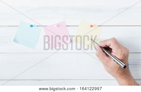 Hand Man Write On Paper Note With Pin On Old White Wood Background.