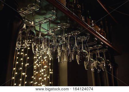 Wine glasses in shelf above a bar rack in restaurant.