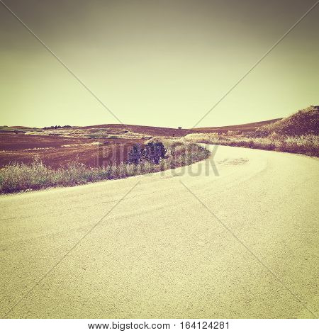 Winding Asphalt Road between Autumn Plowed Fields of Sicily Vintage Style Toned Picture