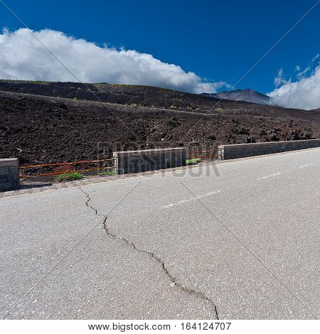 Asphalt Road between the Black Lava Covered Slopes of Mount Etna in Sicily