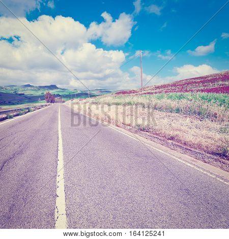 Winding Asphalt Road between Autumn Plowed Fields of Sicily Instagram Effect