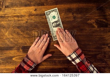 Female hands and one dollar tip cafe bar table top view