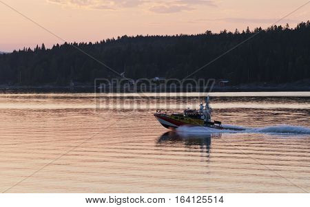 BALTIC SEA, SWEDEN ON JULY 25. View of a Swedish rescue team along the coast on July 25, 2013 of the Baltic Sea, Sweden. Unidentified people in the boat. Sunset. Editorial use.