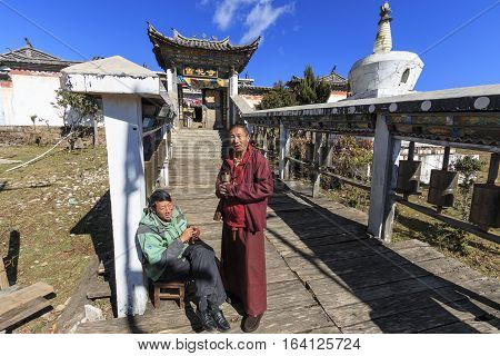 Lijiang China - November 112016: Tibetan Monk and guard in front of a Tibetan Temple in the Dragon Jade Snow Mountain in Yunnan China