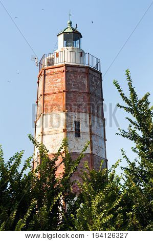 The Cape Shabla lighthouse the oldest on the Bulgarian Black Sea Coast Dobrich Province Bulgaria with its tall hexagonal tower painted red and white for aviation framed by green trees against a blue sky