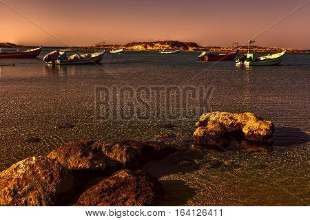 Small motor boats at the beach. Fishing Boats moored in the mediterranean sea in Israel at Sunset.