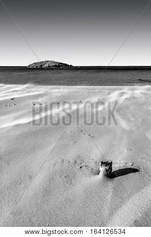 View of a small island from the Israeli shore of the Mediterranean Sea. Sand blowing over beach dune in wind in Israel. Black and White Picture