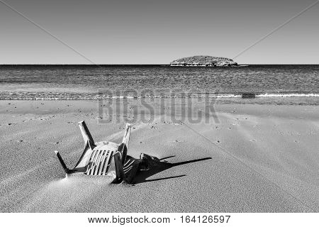View of a small island from the Israeli shore of the Mediterranean Sea. Plastic chair buried in the sand of beach in Israel. Black and White Picture