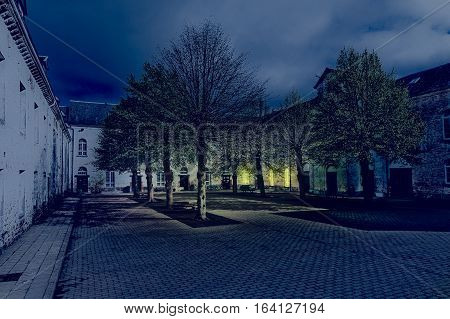 Patio of the Belgian house with park. The old pavement in St Hubert Belgium at night.