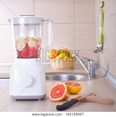 Blender With Sliced Grapefruit On Kitchen Countertop